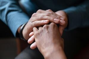 Closeup of a pair of hands gently clasping the hand of another person who is scared and uncertain, symbolizing the dedication of the lawyers at Kain & Scott to make sure you do not feel alone when filing bankruptcy in MN.
